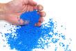 Hand schüttet blaues Granulat