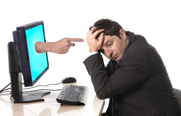 Business man in stress with computer accusing finger pointing