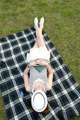 woman sleeping with a hat over her face lying on grass park