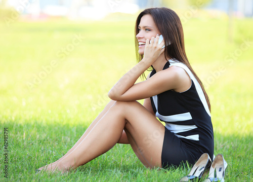 young beautiful smiling business woman sitting on the grass.