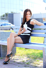 attractive young professional woman drinking coffee in a park
