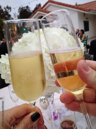 Two people toast their sparkling wine at a celebration.