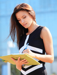Successful businesswoman taking notes while walking outdoor