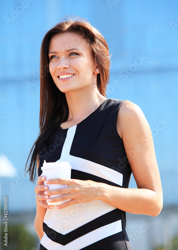 businesswoman professional walking outdoors drinking coffee