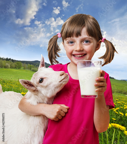 little girl with a goat on a spring meadow.