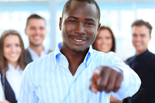 Handsome business man pointing his finger at you