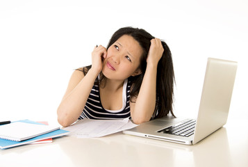 pretty asian woman student overworked on her laptop