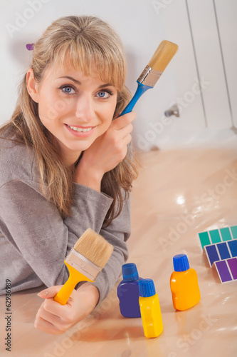 beautiful female painter lies on wooden floor and holding two pa
