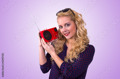 Beautiful woman with red retro radio on her shoulder.