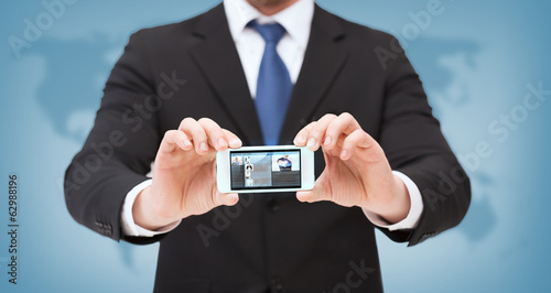 businessman with smartphone and news on screen