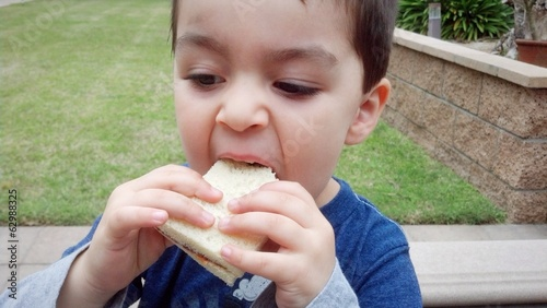 Cute mixed-race boy eating his sandwich outside.