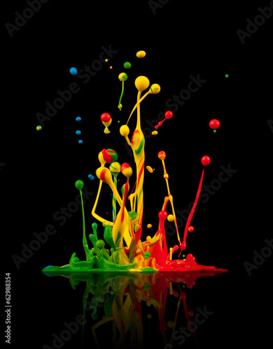 Colored paint splashes on black background