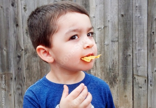 Cute mixed-race young boy eating Potatochip outside.