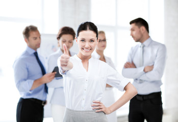 businesswoman in office showing thumbs up