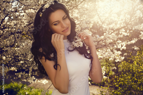 beautiful woman with black hair posing at the spring park