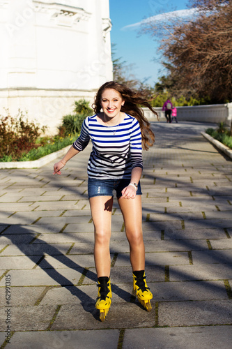 Pretty teenage girl rollerskating in park