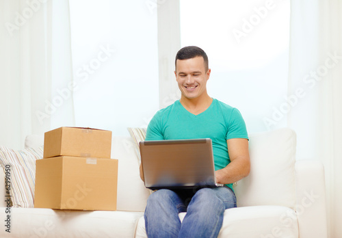 man with laptop and cardboard boxes at home