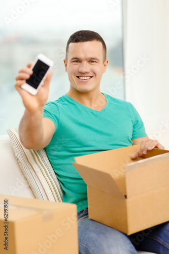 opening cardboard box and taking out smartphone