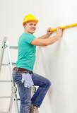 smiling man building using spirit level to measure