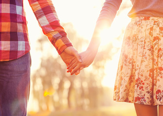 Young couple in love walking in the autumn park holding hands