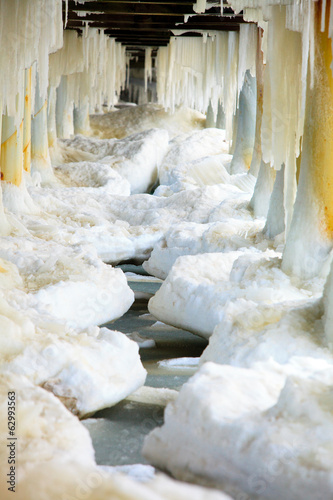 Winter. Baltic Sea. Ice formations icicles on pier poles