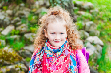 Outdoor portrait of a cute little girl in  early spring