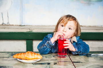 Cute toddler boy having a snack on a terrace in a cafe