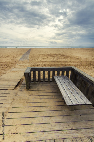 View of wooden passage in a long empty beach shoreline.