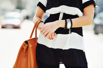 Fashionable woman holding a handbag in hands - close up