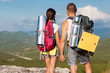 Hikers with backpacks enjoying valley view from top of mountain