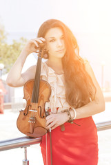 Pretty young woman in red dress with violin in the sunshine.