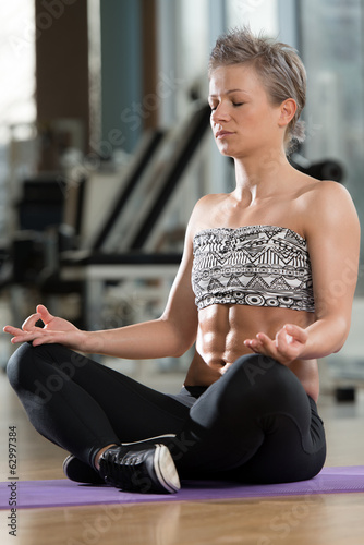 Woman Meditating In A Health Club Doing Yoga