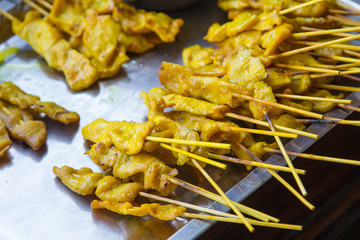Satay chicken on grill.