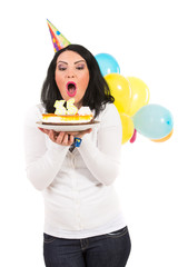 Woman blowing cake candles