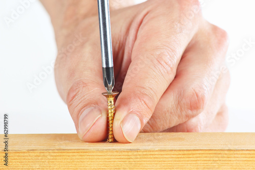 Tightening screws in a wooden block on a white background