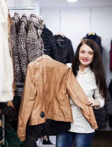 girl choosing jacket at clothing store