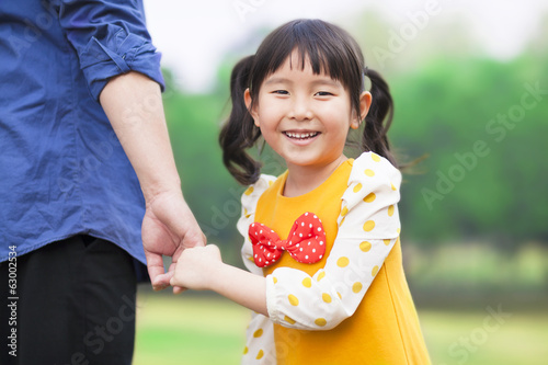 pretty girl hold father hand in the park