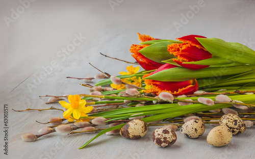 Yellow daffodils, red tulips and willow twigs near the quail egg