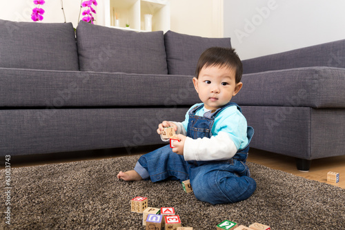Asia baby boy play wooden toy block at home