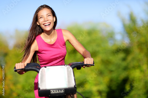 Asian woman on bike biking in city park