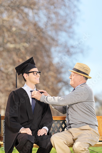 College student and his proud father sitting in park