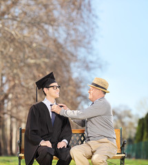Graduate student and his proud father sitting in park