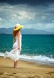 Lonely woman in a white dress standing at the sea shore and watc