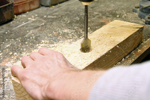carpenter drilling in a wooden board