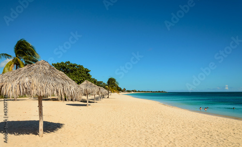 Caribbean beach with sun, palm tree umbrella, playa Ancon, Cuba
