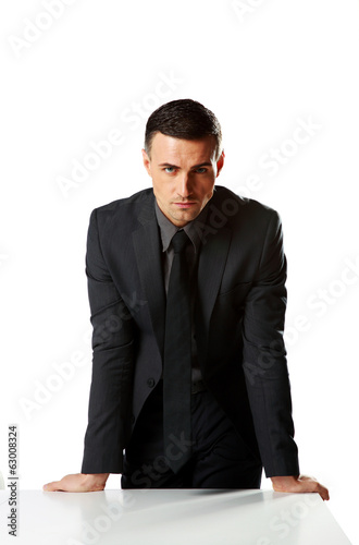 Confident businessman leaning on the table