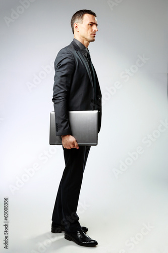 Full-length portrait of a pensive businessman standing