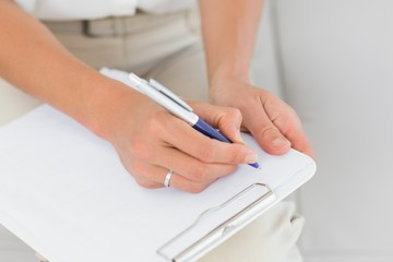 Therapist taking notes on clipboard