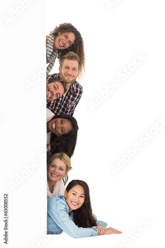 Happy group of young friends peeking from behind a wall
