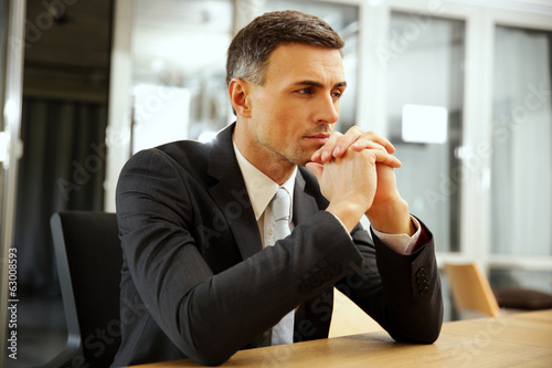 Pensive businessman sitting at office